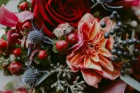 an extra bold fall wedding bouquet of deep red, fuchsia and orange blooms, berries, thistles and greenery is amazing to rock