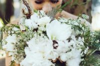 an extremely textural cotton wedding bouquet with white blooms, smaller wildflowers, greenery and twigs is a lovely idea for a woodland bride