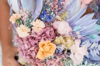 an iridescent edding bouquet composed of lilac fronds, pink and orange blooms, pink hydrangeas and bunny tails plus foliage