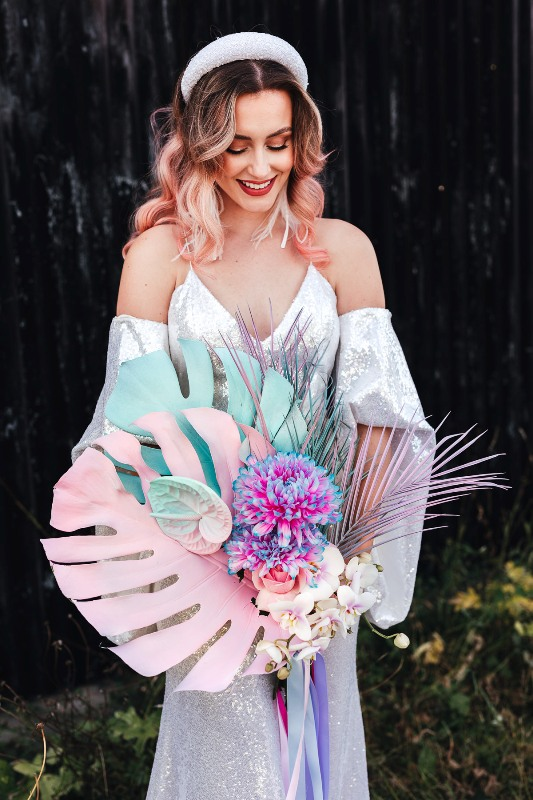 an iridescent wedding bouquet of blue and blush spray painted tropical fronds, iridescent blooms and leaves and colorful ribbons