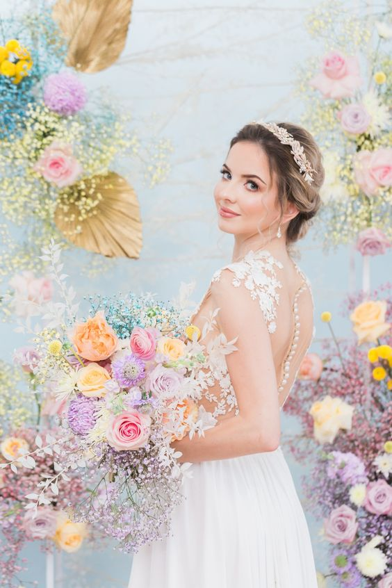 an iridescent wedding bouquet of pink, yellow, peach, lilac and purple blooms and baby's breath is a gorgeous solution