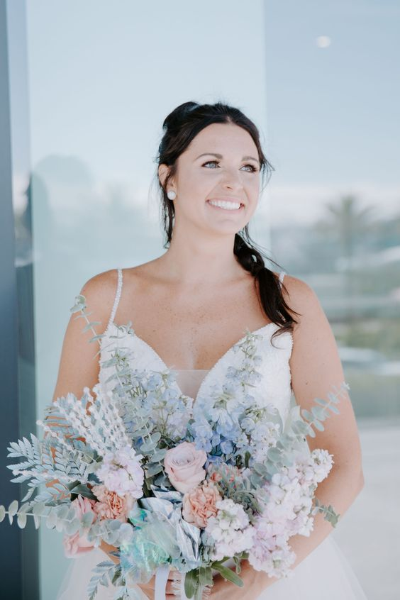 an iridescent wedding bouquet with blue, blush and peachy blooms, pale greenery and ribbons is a very lovely idea to rock