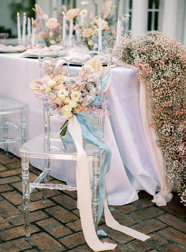 an iridescent wedding bouquet with blush, blue, white and iridescent blooms and long ribbons is wow