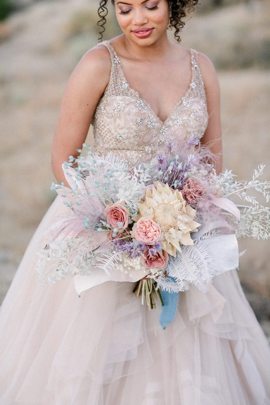 an iridescent wedding bouquet with fresh and dried blooms and fronds plus blue ribbons is a very cool and chic idea to rock