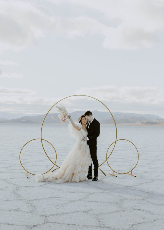 an ultra minimalist wedding altar of gilded circles on stands, with a fantastic view of Salt Flats is wow