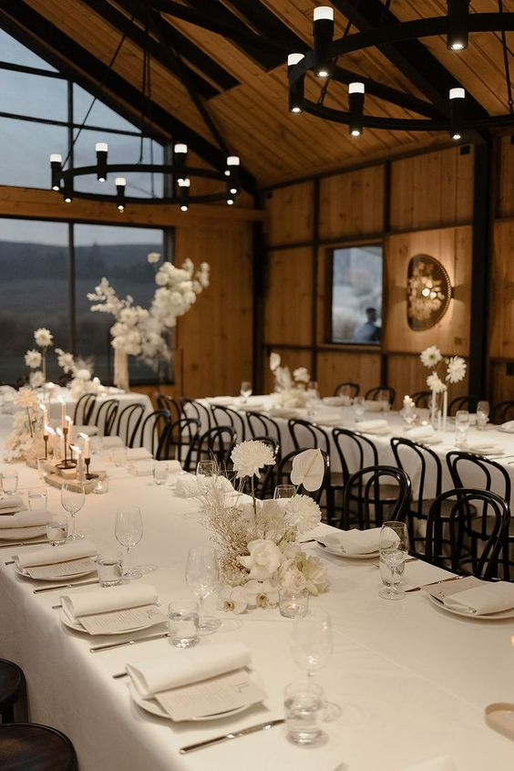 beautiful all-neutral minimalist wedding tablescapes with white blooms, white linens and menus, candles are gorgeous