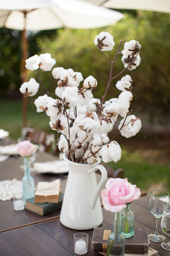cotton branches in a jug, pink roses and vintage books for decorating the wedding tablescape and giving it a cozy feel