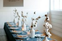modern wedding centerpiece of white vases with cotton branches can be rocked at any boho wedding, in the fall or winter