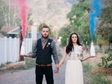 a fun and cool idea of a wedding portrait with a pink and blue smoke bomb to accent the couple