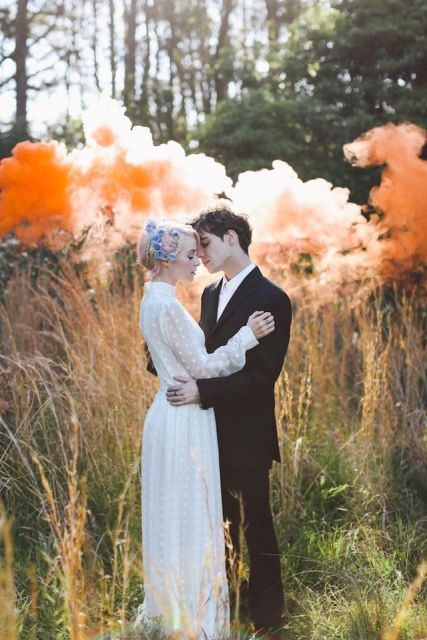 a beautiful wedding portrait in the forest with orange smoke bombs looks bold and very eye catchy