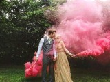 hot pink smoke bombs accent the couple and make it stand out in the greenery backdrop