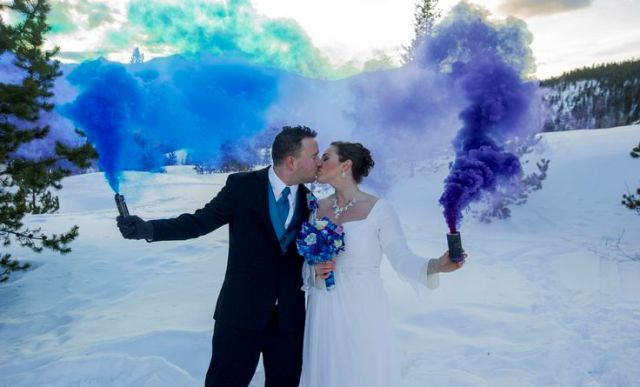 a blue and purple smoke bomb accent the couple in the snow backdrop and make it stand out