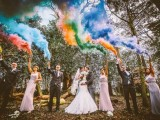 a wedding photo in the forest accented with lots of colorful smoke bombs instead of usual confetti or petals