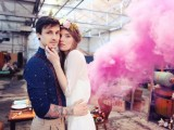 an industrial wedding space turned into a romantic one with a pink smoke bomb becomes a lovely backdrop for a wedding portrait