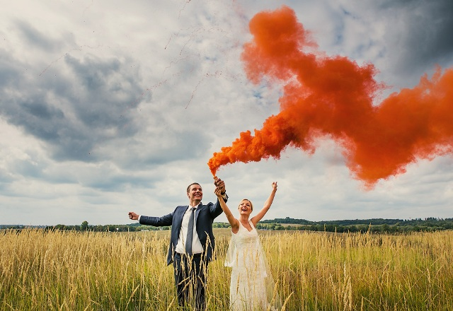 a beautiful wedding portrait in the field with an orange smoke bomb is a lovely and fun idea for a wedding
