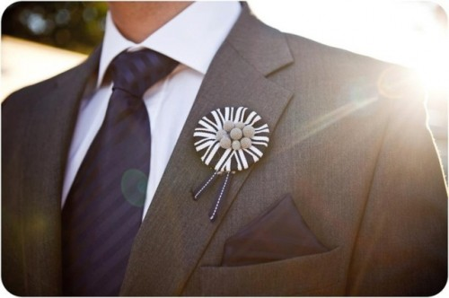 a bold black and white wedding boutonniere with ribbons and buttons is a lovely and fun idea