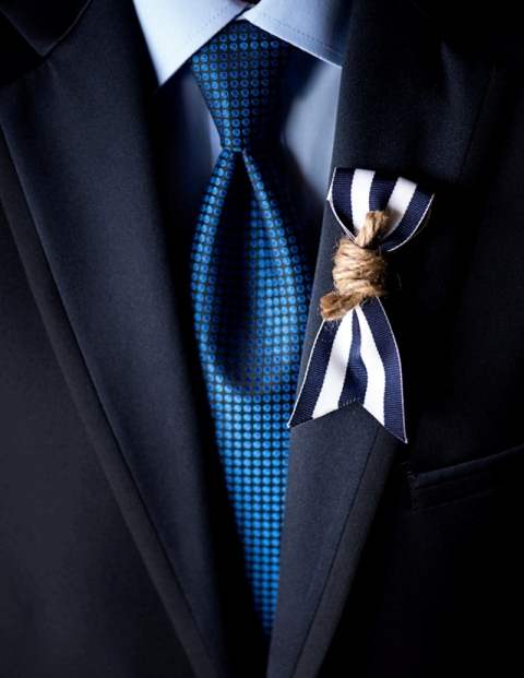 a nautical wedding boutonniere of a striped ribbon piece and rope is lovely and chic