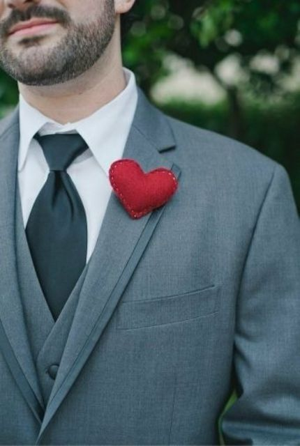 a red heart-shaped boutonniere is a nice way to give a more romantic and whimsy touch to a groom's look