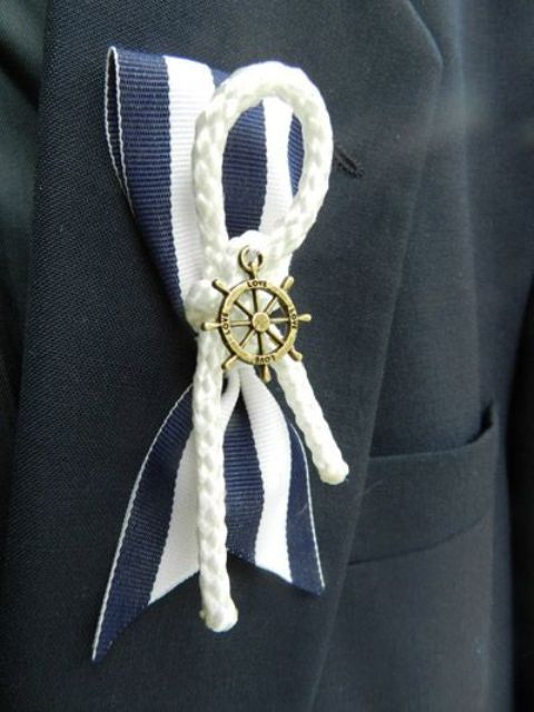 a nautical wedding boutonniere of a striped ribbon piece, rope and a wheel is fun and cool