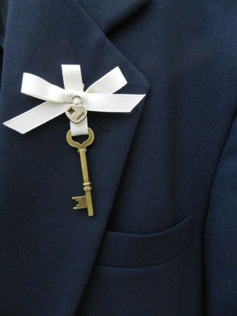 a refined wedding boutonniere of a vintage key, a mini heart-shaped lock and a white ribbon bow