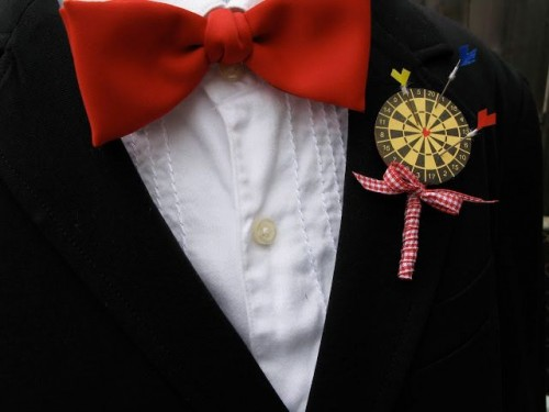 a colorful darts boutonniere with bright arrows and ribbon is a fun and playful accessory idea