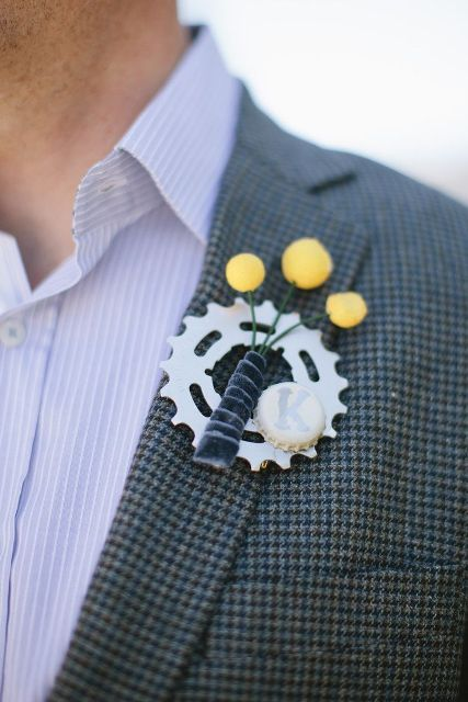 a creative gear wedding boutonniere with billy balls and a bottle lid with a monogram is a fun and cool idea to try