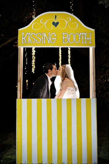 a bold yellow and white kissing booth with a stripe pattern is a fun idea for a modern wedding