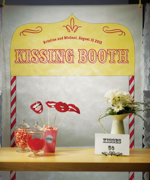 a bright kissing booth and dessert table in one, with flowers, a sign, props and lots of tasty sweets