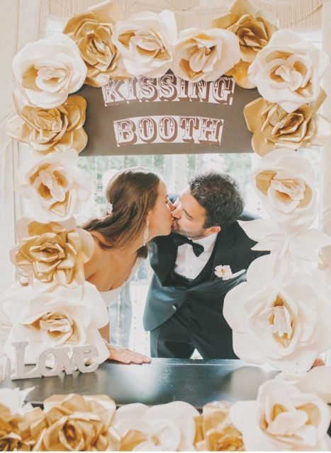 a simple wedding kissing booth with large fabric blooms and a sign plus LOVE letters for a classic wedding