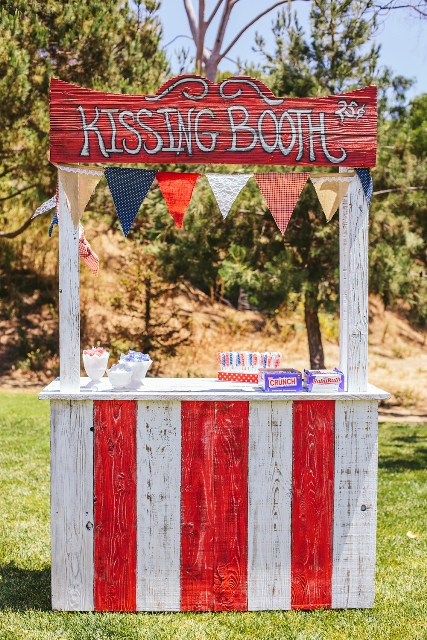 a colorful kissing booth of painted wood, with a bright bunting and various sweets