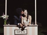 a simple and cute wedding kissing booth done in pink and white stripes, some blooms and a sign over it