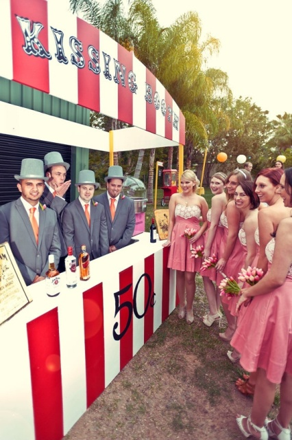 a large and colorful striped kissing booth that doubles as a wedding bar is a cool and bold idea for a wedding