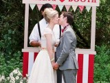 a bright striped kissing booth with a colorful bunting and potted blooms next to it