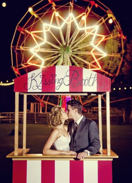 a brigth striped kissing booth placed strategically to create a cool and fun wedding backdrop