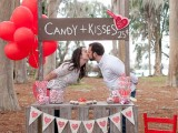 a kissing booth dessert table made of pallets, a sign on top, a heart banner and bright red balloons