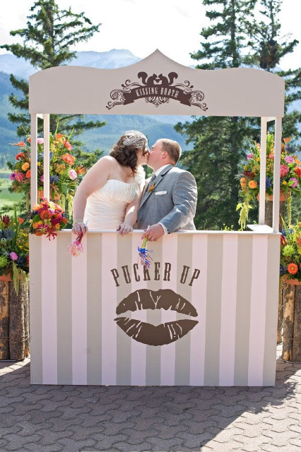 a neutral striped kissing booth decorated with bright blooms and with the same flowers as a backdrop for fun