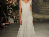 an embellished wedding dress with thick straps and pleated all over the dress is very chic and refined