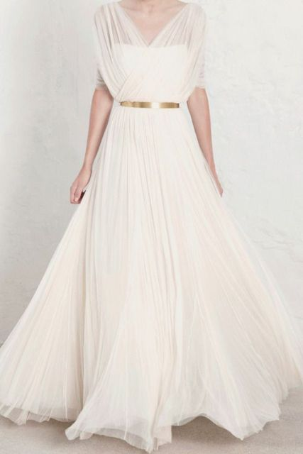 an a-line wedding dress with a pleated semi sheer overdress and a gold belt for a refined and chic look