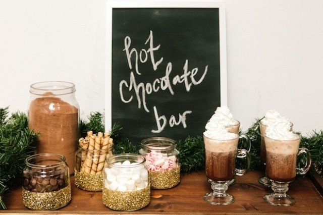 a cozy and cute hot chocolate bar with a chalkboard sign, glittered jars with sweets and candies and evergreens