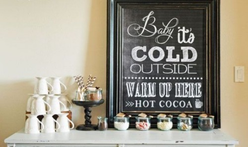a small and simple hot chocolate bar with a chalkboard sign, some mugs and delicious candies in jars