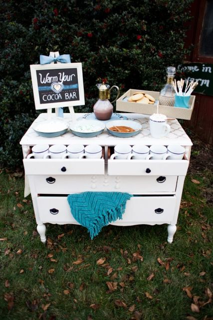 a simple and nice hot cocoa bar of a white sideboard, with a blanket, a sign, a tray with cookies and a carafe