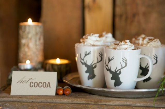 a small hot cocoa bar with a tray with deer mugs, a card and some candles in branch candleholders