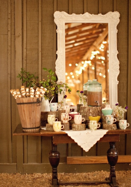 a rustic vintage hot cocoa bar done with a vintage table, tree stumps, greenery in a jug and a vintage mirror and doily