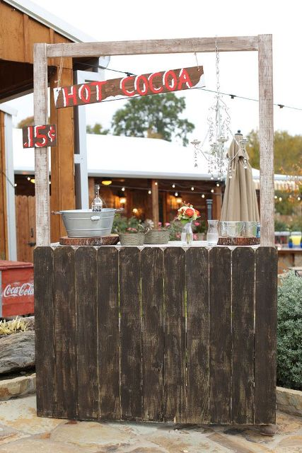 a rustic hot cocoa bar with a wooden board stand, wood slices, wood signs, buckets with everything necessary