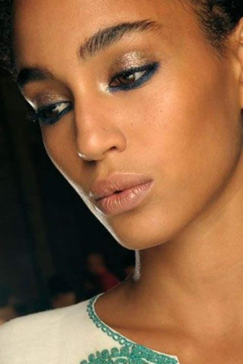 a shiny makeup with a glowing blush lip, gold eyeshadows, blue eyeliner and brushed eyebrows