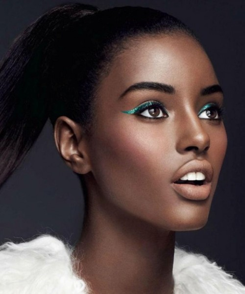 a fashion-forward makeup with a matte nude lip, aqua eyeliner, a touch of blush and a perfect skin tone