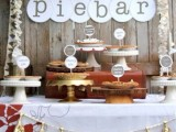 a cozy rustic pie bar with paper garlands, a letter banner, mismatching stands including a rustic one with a wood slice and a garland with gold tassels is ideal for a fall wedding