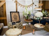 a rustic pie bar with a banner, some simple blooms, signs and tags, candles and pies on stands and plates