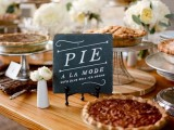 an elegant pie bar with white blooms and greenery, with a chalkboard sign, pies on glass and metal stands is very chic