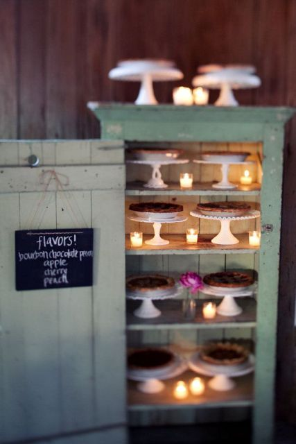 a vintage mint colored cabinet with candles and chalkboard signs and pies on stands is a cool idea for a vintage or rustic wedding
